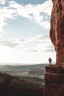 Een persoon die aan de rand van een klif, omringd door heuvels en bergen onder een heldere hemel