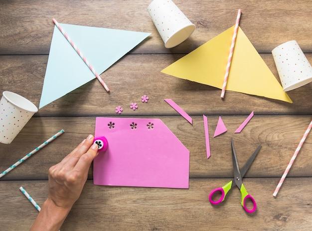 Een persoon die bloemenontwerp op roze document over de lijst ponsen