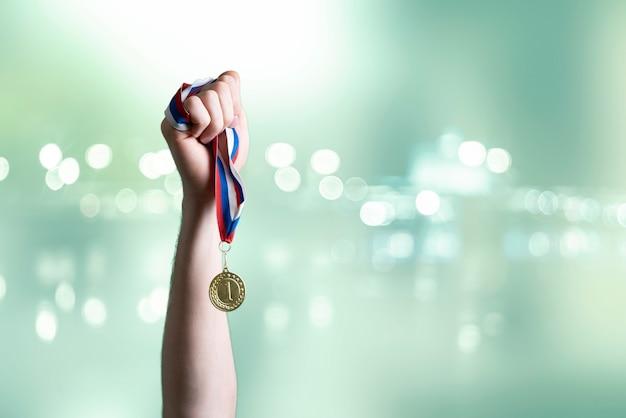 Een persoon die de hand opsteekt en de eerste plaats wint, houdt een gouden medaille vast!