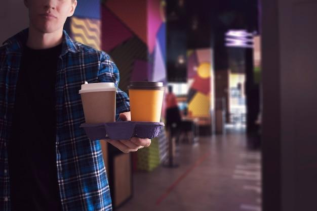 Een persoon die een dienblad met een paar koffiekopjes vasthoudt