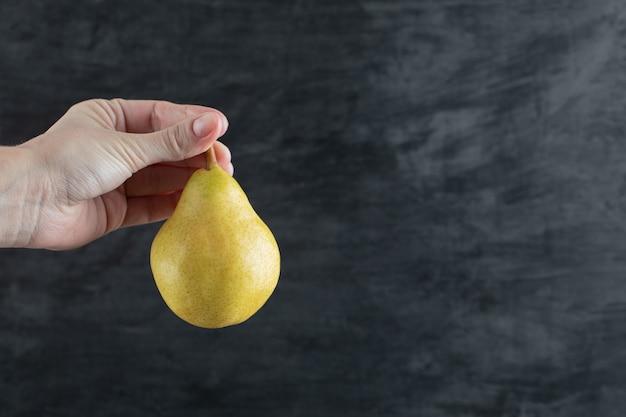 Een persoon die een gele peer van de stengel vasthoudt