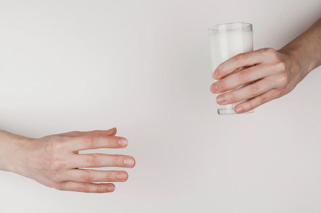 Een persoon die een glas melk aan een ander overhandigt