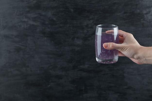 Een persoon die een glas paars sap vasthoudt