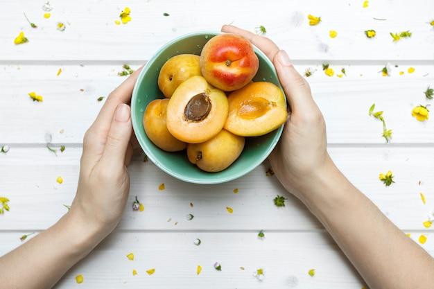 Een persoon die een groene kom van perziken met gele bloemen houdt die op een houten oppervlakte worden uitgespreid