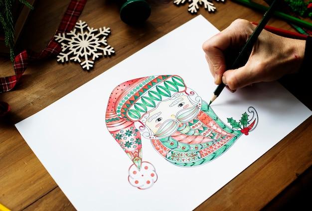 Een persoon die een kleurrijk gezicht van de kerstman trekt