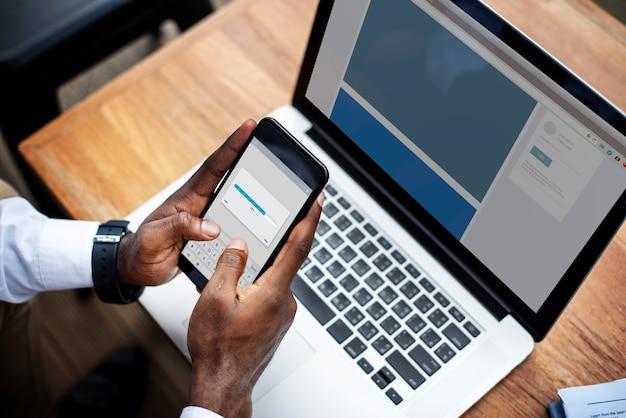 Een persoon die een mobiele telefoon en een laptop gebruikt