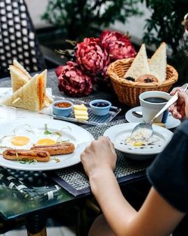 Een persoon die een ontbijt aan tafel eet