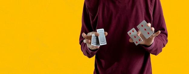 Een persoon die een paar speelkaarten vasthoudt en de focus van de goocheltruc doet, staande angaist de wall wide webn banner