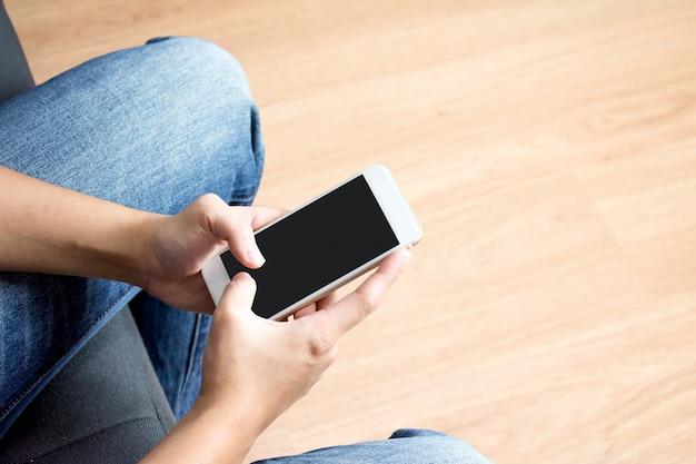 Een persoon die een telefoon op een bank in het bovenaanzicht van een man met een shirt en spijkerbroek in de kamer.