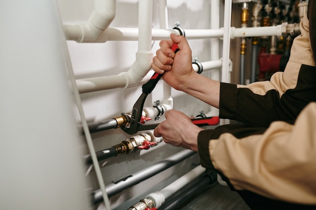 Een persoon die een van de gereedschappen gebruikt tijdens het repareren of repareren van delen van pijpen