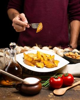 Een persoon die gebakken aardappel met een vork neemt.