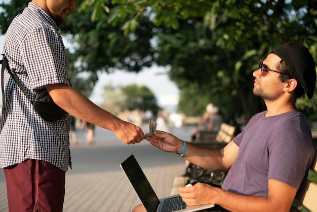 Een persoon die geld geeft en de nieuwe laptop koopt