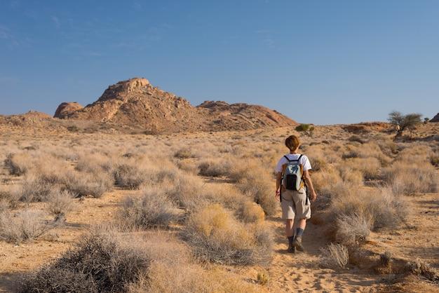Één persoon die in de namib-woestijn wandelt, het nationale park van namib naukluft, namibië. avontuur en verkenning in afrika. heldere blauwe lucht.