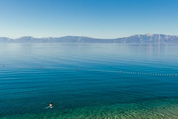 Een persoon die in het blauwe idyllische meer zwemt