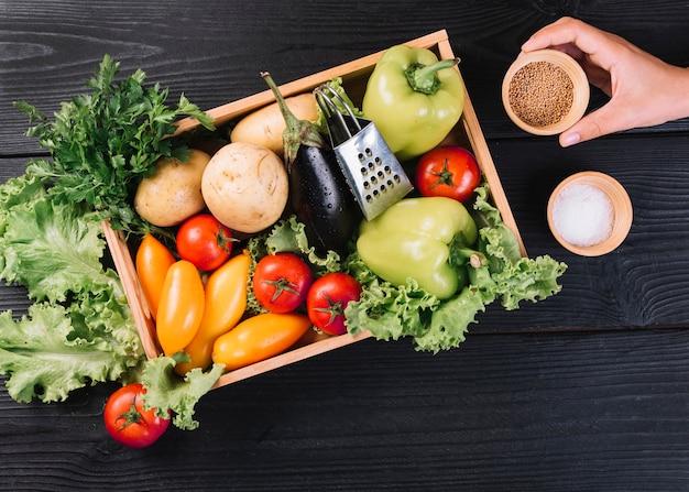 Een persoon die kom mosterdzaad houdt dichtbij verse groenten in container op zwarte houten lijst