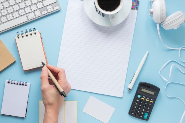 Een persoon die op blocnote met pen op bureau blauw bureau schrijft