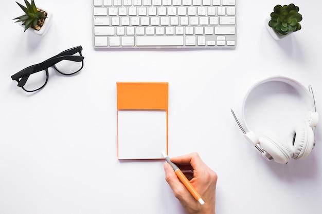 Een persoon die op kleverige nota's met pen op witte werkruimte schrijft