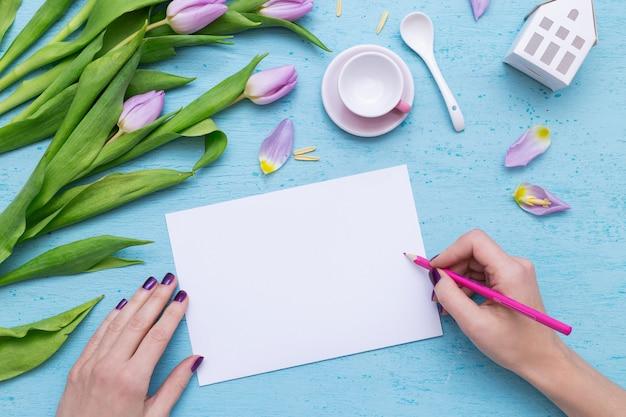 Een persoon die op wit papier tekent met een roze potlood in de buurt van paarse tulpen en een koffiekopje