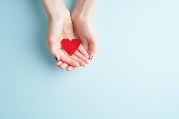 Een persoon die rood hart in handen houdt