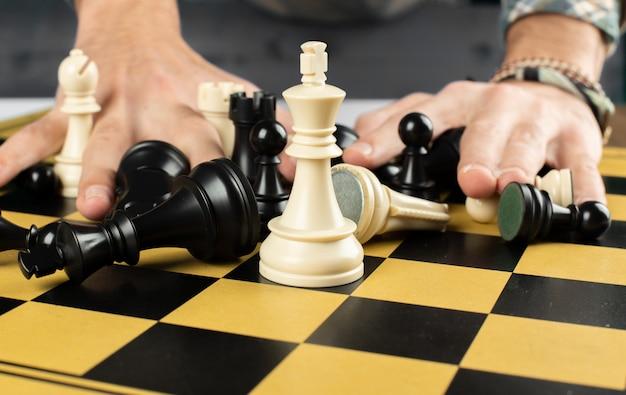 Een persoon die schaakfiguren mengt