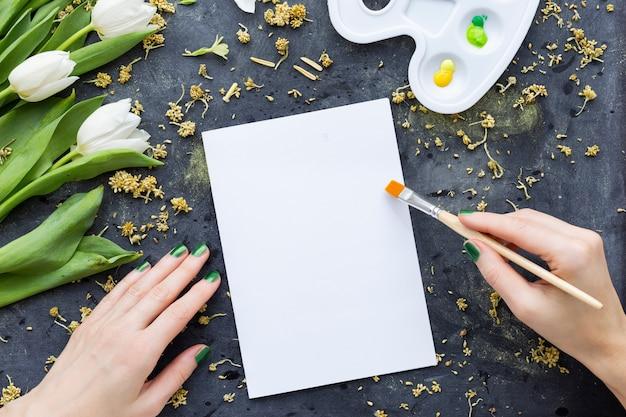 Een persoon die schildert op een wit papier in de buurt van witte tulpen op een zwart oppervlak