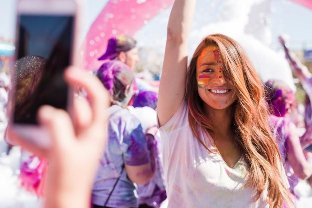 Een persoon die selfie van haar glimlachende vrouwelijke vriend op mobiele telefoon tijdens holi neemt