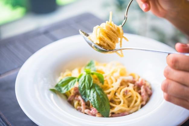Een persoon die smakelijke spaghetti houdt die op vork wordt gerold
