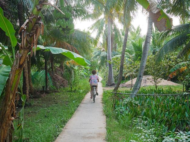 Een persoon fietst in de mekong delta-regio, ben tre, vietnam