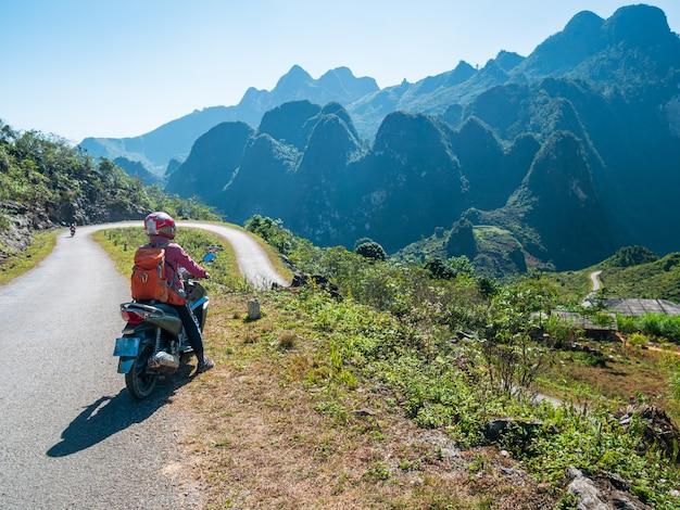 Een persoon fietst op ha giang motorlus, beroemde reisbestemming bikers gemakkelijke rijders. ha giang karst geopark berglandschap in noord-vietnam