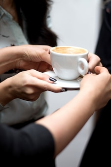 Een persoon heeft een kopje cappuccino
