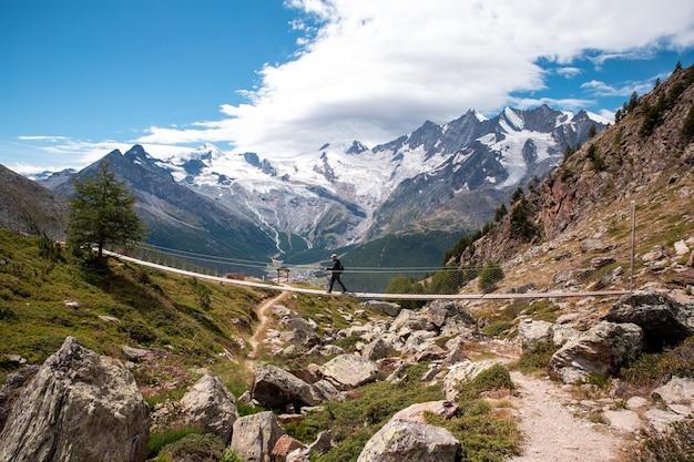 Een persoon jongeman loopt op een hangbrug in zwitserland, wandelen met een prachtig landschap
