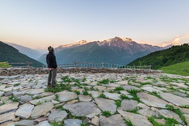 Eén persoon kijkt hoog in de alpen naar de zonsopgang