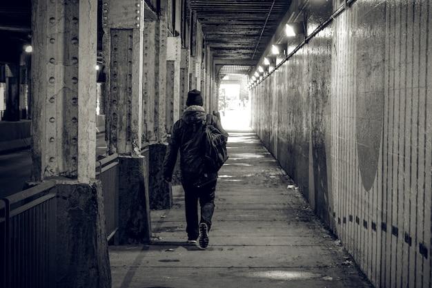 Een persoon loopt door een donkere tunnel in een grote stad, op weg naar het licht.