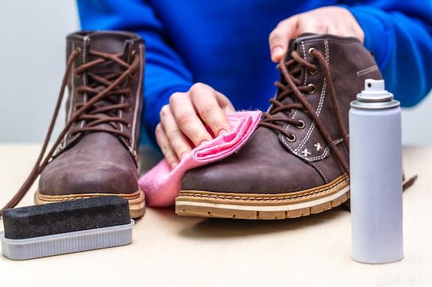 Een persoon maakt casual suède herenlaarzen schoon met borstel, doek en spray. schoensmeer. schoeisel vocht- en vuilbescherming