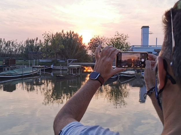 Een persoon maakt een foto van de zon in een herfstzonsondergang