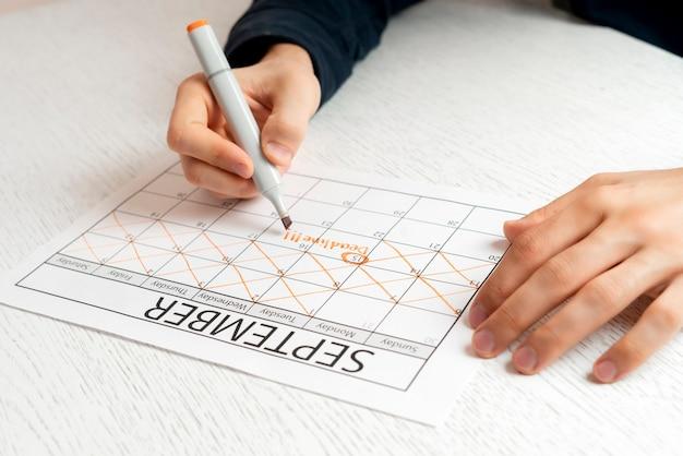 Een persoon maakt een kruisje op de datum in de kalender, maakt aantekeningen
