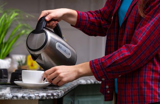 Een persoon maakt thee met kokend water uit een waterkoker in de keuken thuis