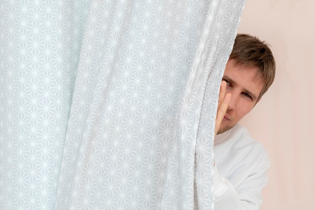 Een persoon met half bedekt gezicht houdt toezicht op gluren en spioneren, de uitkijk