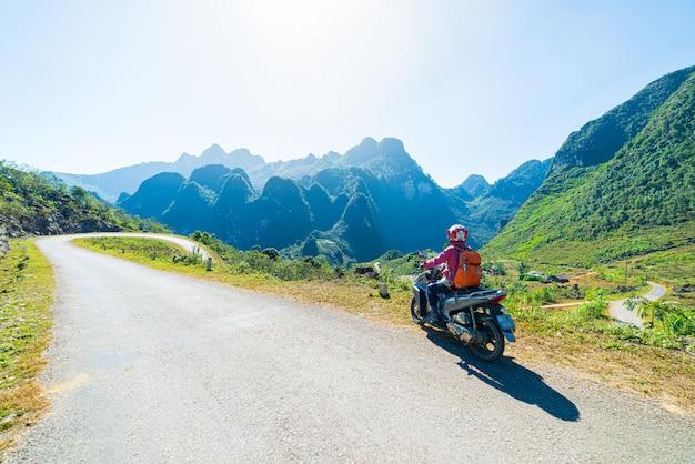 Eén persoon op de fiets op ha giang motorlus, beroemde reisbestemming motorrijders easy riders. ha giang karst geopark berglandschap in noord-vietnam. bochtige weg in een prachtig landschap.