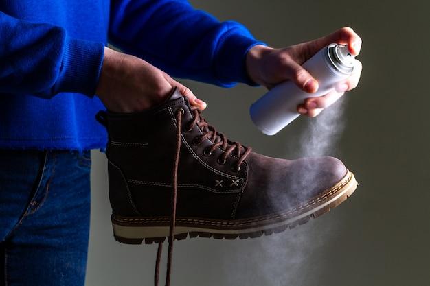 Een persoon reinigt en spuit op casual suède laarzen voor heren ter bescherming tegen vocht en vuil. schoensmeer
