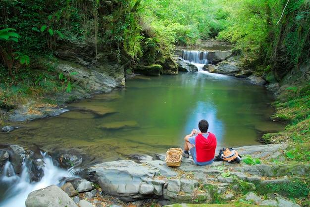 Een persoon rust naast een rivier en een waterval met een mandje noten in het natuurpark van gorbeia