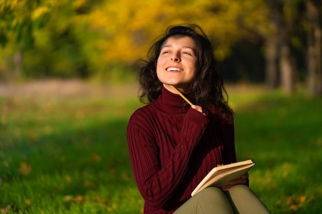 Een persoon schrijft notities zittend op een gazon in een herfstpark