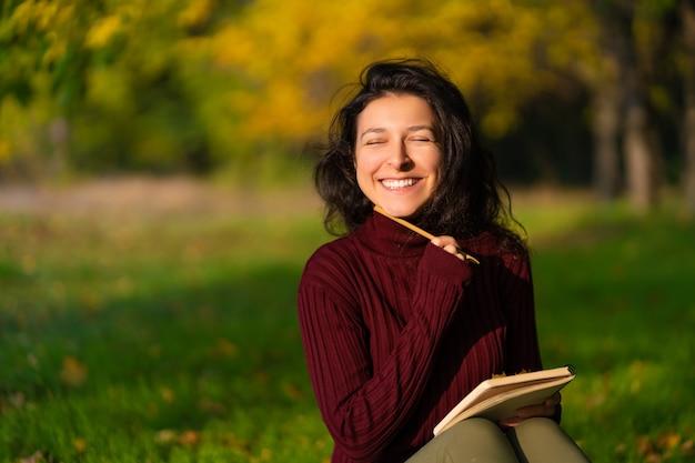 Een persoon schrijft notities zittend op een grasveld in een herfstpark. vrolijke gemoedstoestand. zoeken naar inspiratie.