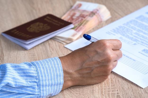 Een persoon sluit een verzekering af en geeft een onderzoek door. op de tafel ligt een paspoort en een bundel bankbiljetten