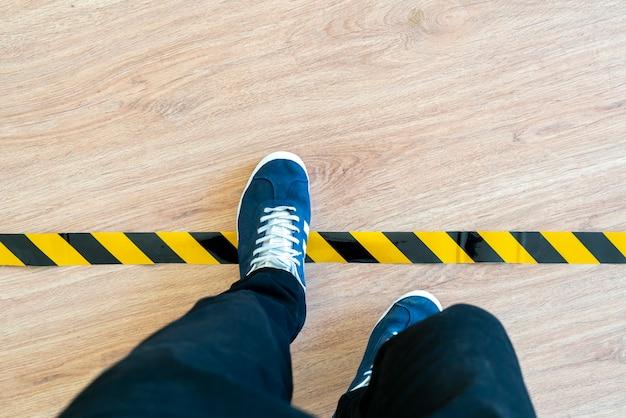 Een persoon steekt de zwarte en gele stoplijn over en remt het limietconcept