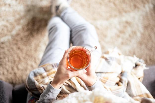 Een persoon thuis met thee