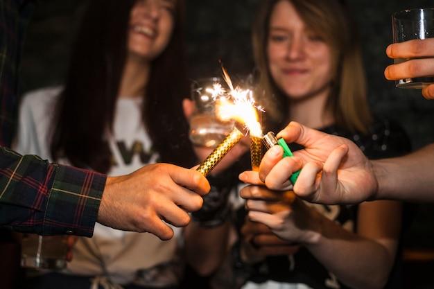 Een persoon verlichting sprankelt kaars met aansteker met vrienden