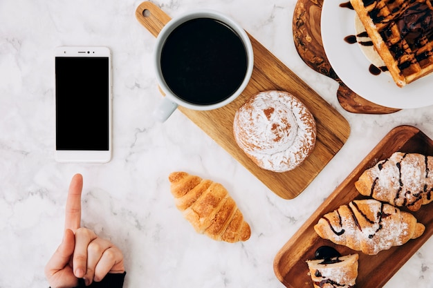 Een persoon wijzende vinger naar mobiel en gebakken broodjes; croissant; wafels en een koffiekopje op het bureau