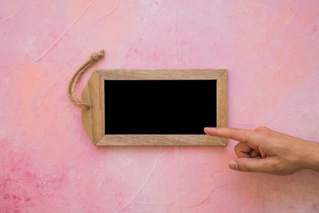 Een persoon wijzende vinger op kleine tag leisteen op roze geschilderde achtergrond