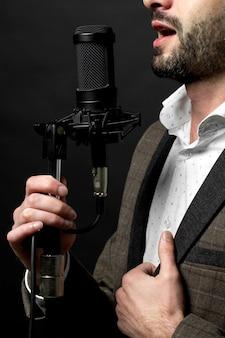 Een persoon zingt voor een staande microfoon